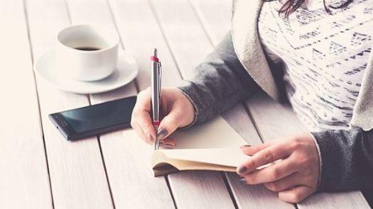 Frau am Schreibtisch mit Notizheft und Kaffee