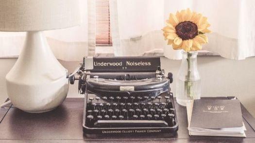 Schreibtisch mit Notizbuch, Schreibmaschine und Sonnenblume