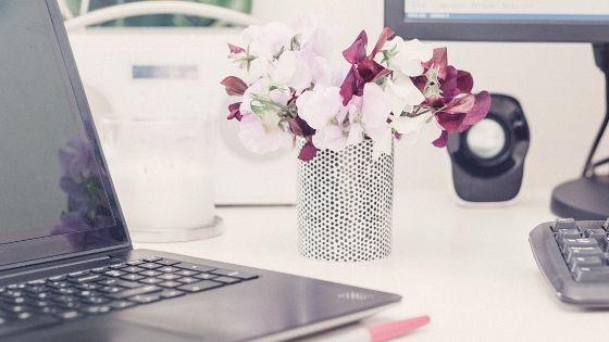 Schreibtisch mit Laptop und Blumen
