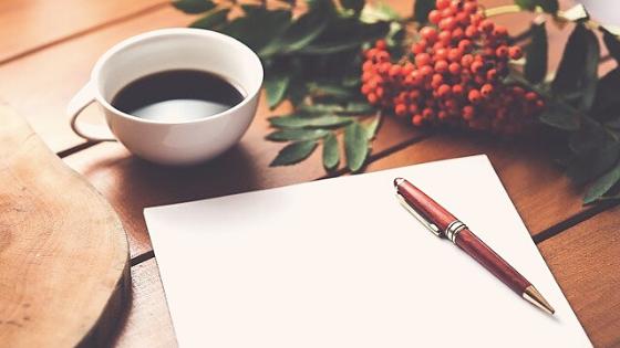 Schreibpapier, Stift und Kaffee